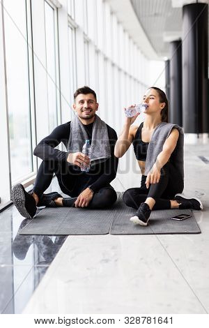 Young Couple Relax After Training Frink Water At Gym