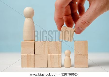 Male Hand Closes Small Wooden Figure By Blocks Under The Supervision Of Another Figure On Blue Backg