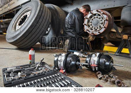 Truck repair service. Mechanic works with brakes in truck workshop