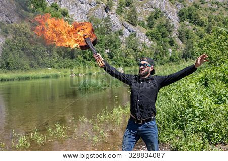 23 Year Old Guy With A Beard In A Black Shirt, Cap And Sunglasses Holds A Burning Guitar. Against Th