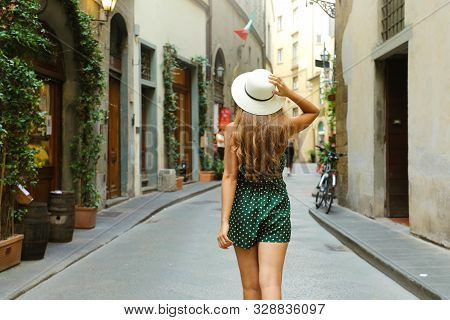 Back View Of Tourist Woman Walking In Florence Street, Italy. Rear View Of Cheerful And Happy Girl I