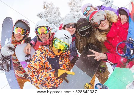 Big Group Of Friends Is Having Fun At Ski Resort. Happy Skiers And Snowboarders Are Taking Photo Tog
