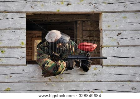 Active Paintball Game. Paintball Player In Protective Uniform And Mask Sight In A Forrest Case