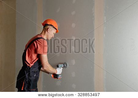 The Worker Is Making Holes In The Drywall To Install The Outlet In The Future.