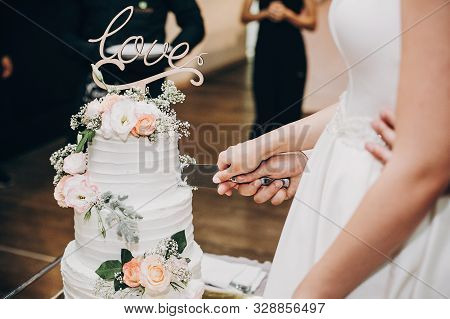 Bride And Groom Cutting Stylish Wedding Cake At Wedding Reception In Restaurant. Wedding Couple Hold