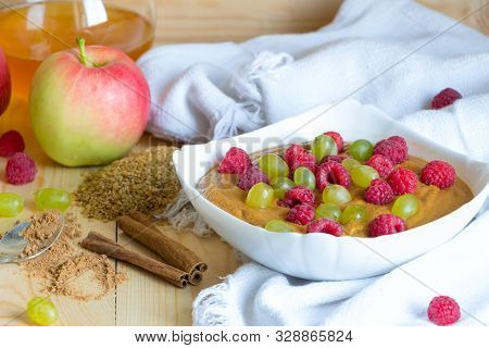 Healthy Meal Concept Background. Vegan Flax Porridge With Raspberry And Grape Raisins In White Bowl