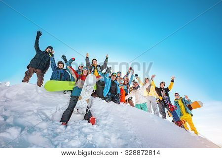 Big Group Of Happy Skiers And Snowboarders With Raised Arms Stands On Snowdrift At Ski Resort. Ski A