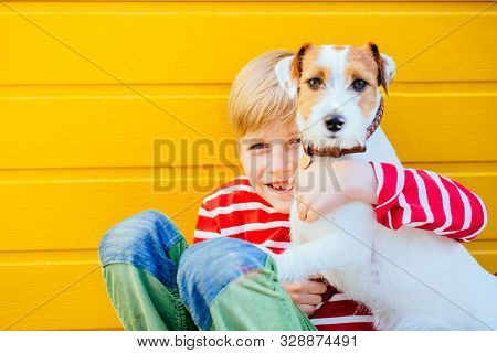 Portrait Of Happy Preteen Boy Sitting On The Ground Playing With His Dog Jack Russell Terrier On Yel