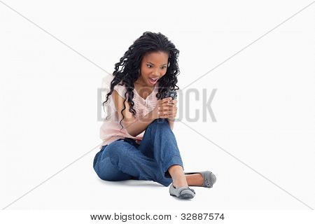 A surprised young woman is sitting on her floor looking at her mobile phone against a white background