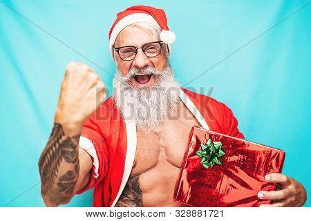 Happy Fit Santa Claus Holding Christmas Present - Hipster Senior Having Fun Celebrating X-mas Holida