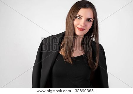Portrait Of A Young Beautiful Girl On A White Background, Black Jacket Thrown Over Her Shoulders, St