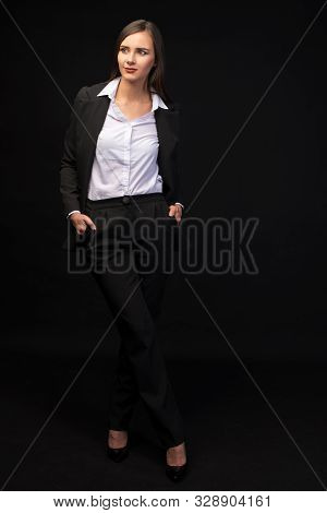 A Young Beautiful Girl In A Full-length Business Suit On A Black Background, A Beautiful Brunette In