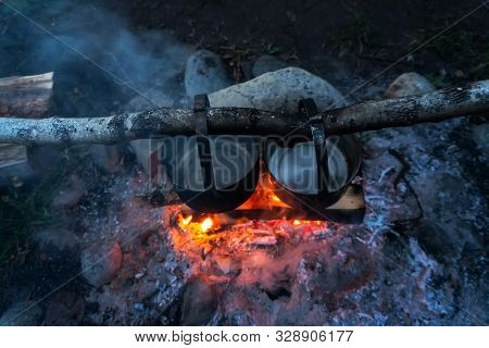 Top View Of Two Metal Pots Above The Fire In The Woods. Cooking Dinner In A Travel.