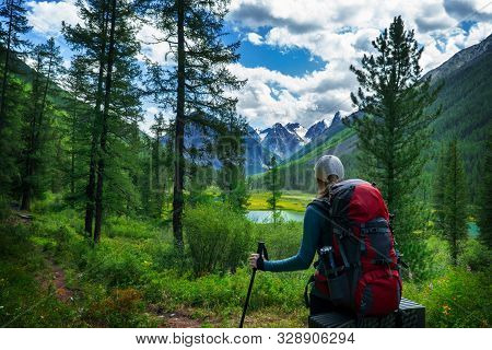 Girl Tourist With Backpack And Poles Looking At The Beautiful Summer Landscape With Mountain Peaks.