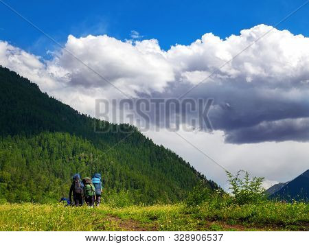 A Group Of Tourists With Backpacks Walking In The National Park. Beautiful And Inspiring Landscape.