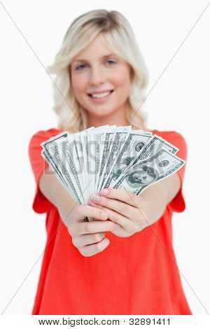 A fan of dollar notes held by a smiling attractive woman against a white background