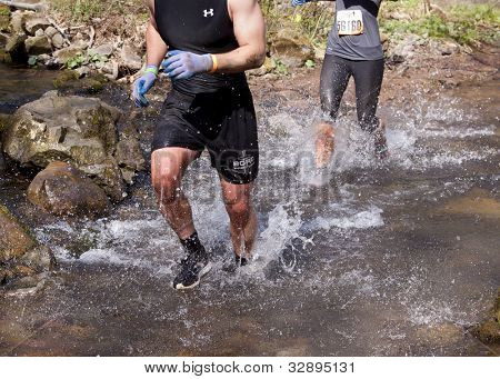 POCONO MANOR, PA - APR 28: Participants run through a flowing cold water creek at Tough Mudder on April 28, 2012 in Pocono Manor, Pennsylvania. The course is designed by British Royal troops.