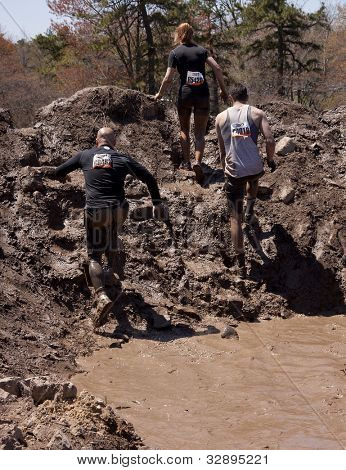 POCONO MANOR, PA - APR 29: Participants walk through several pits of mud and water at Tough Mudder on April 29, 2012 in Pocono Manor, Pennsylvania. The course is designed by British Royal troops.