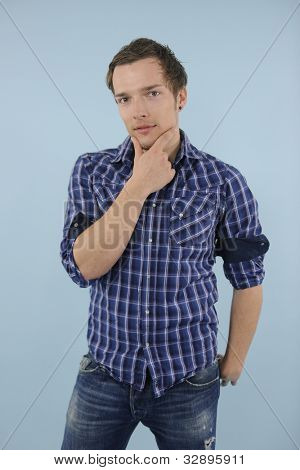 portrait of a casual man thinking on blue background