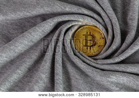 Golden bitcoin shiner on gray cotton cloth with swirl crumpling poster