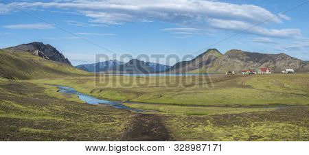 Panoramic landscape with mountain huts at camping site on blue Alftavatn lake with river, green hills and glacier in beautiful landscape of the Fjallabak Nature Reserve in the Highlands of Iceland part of Laugavegur hiking trail. poster