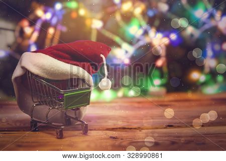 Christmas Shopping X-mas Sale Concept. Shopping Cart And Santa Cap Against Decorated With Festive Li