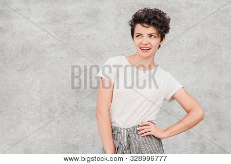 Charming Young Woman With Creative Hairstyle Is Smiling And Posing With Intrigued And Surpriesed Fac