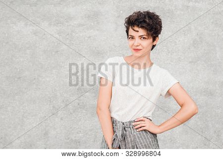 Charming Young Woman With Creative Hairstyle Is Posing With Intrigued And Surpriesed Face.