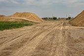 excavator summarizes soil on construction site in dry summer season poster