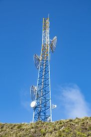 Cell Tower On Top Of A Mountain Against The Blue Sky