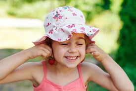 Portrait Of Cute Little Girl In Big Hat Is Eating Strawberries At Summer Day