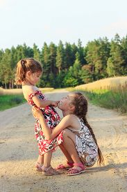 Two Cute  Little Girls Smiling And Playing At The Field In Warm Summer Day. Happy Childhood Concept