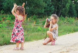Cute Little Girls Taking Pictures With Old Film Camera Outdoor.  Pretty Children In Nature.