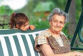 Grandmother With Grandchild - Senior Woman Taking And Smiling With Her Granddaughter Outdoor