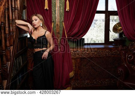 Wealthy middle-aged woman with evening makeup and hairstyle stands in black glamorous look in a luxury apartment. Luxury lifestyle.