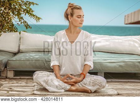 Nice Calm Female with Closed Eyes Sitting in Lotus Pose on the Terrace of Beach House. Meditating on the Beach. Zen Balance. Peaceful Summer Vacation.