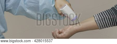 Banner With Female Nurse Wearing Disposable Medical Suit Checks Patient's Body Temperature With Amed