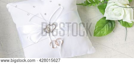 Banner With White Rose And Pillow With Rhinestone Hearts For Wedding Rings With Rings On White Backg