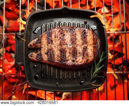 Roasted salmon steak in frying pan on bbq grate over hot pieces of coals. Top view.