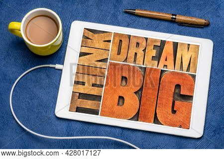 think and dream big motivational phrase -  word abstract in letterpress wood type printing blocks on a digital tablet with coffee