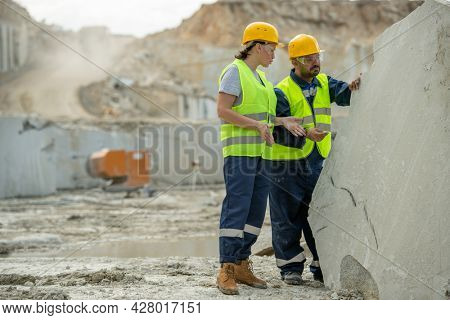Two builders in hardhats and workwear discussing working points by huge block