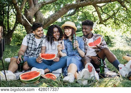 Group Of Four Multiracial Friends Using Modern Smartphone, Eating Watermelon And Drinking Beer. Happ