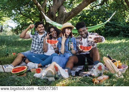 Young Multiracial People Using Modern Smartphone For Taking Selfie At Green Garden. Four Cheerful Fr