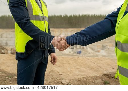 Handshake of contractor and female builder against construction site