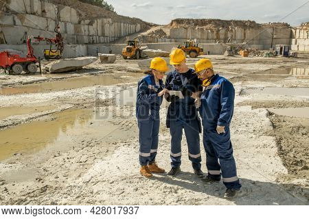 Three builders in workwear discussing sketch of building in tablet