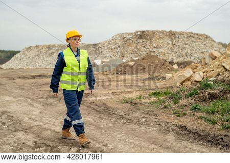 Confident female employer in workwear moving along construction site or quarry