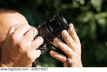Close-up Of A Photographer Holding A Digital Camera And Photographing Something Outdoors On A Sunny