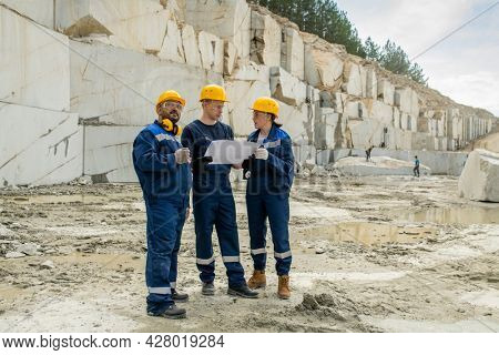 Team of contemporary miners in workwear discussing blueprint at quarry