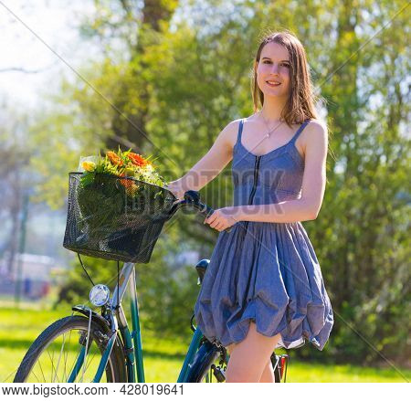 Young woman in short grey dress with long hair rides a bicycle with basket and flowers tour summer city park, look and smile on flowers bouquet