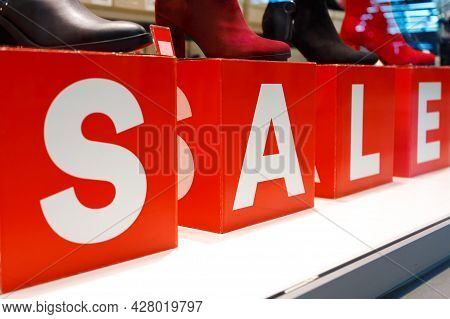 Shoes Store Showcase Window Big White On Red Sale Close-up Advertisement Text On Cubes In Store Mall